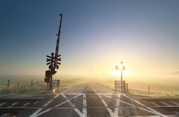 mistig Sunrise over Railway Crossing op Nederlandse landbouwgrond foto