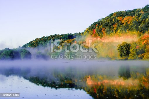 Foggy sunrise with fall color reflection on St Croix river at Interstate Park, MN