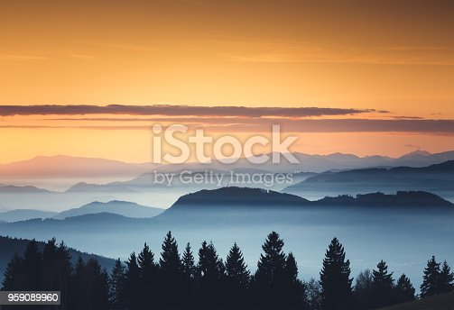 Foggy mountain landscape at sunset.