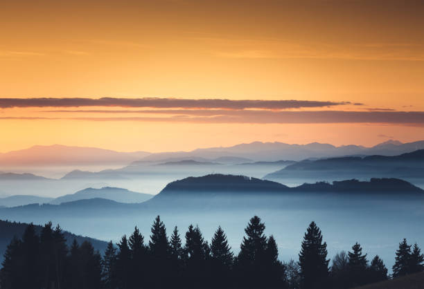 foggy sunset - mountain sunset stock photos and pictures