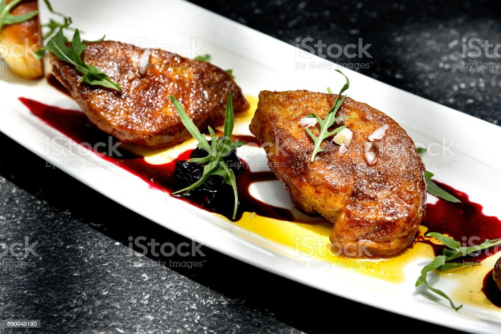 Foie gras grilled served with red berries sauce and chestnut. stock photo