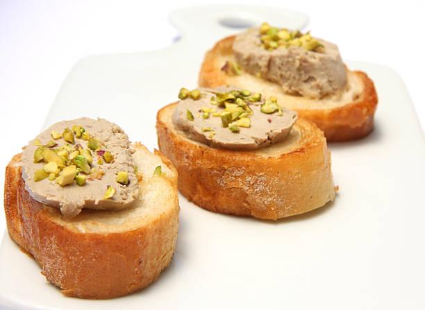 Foie gras on baguette with pistachio stock photo