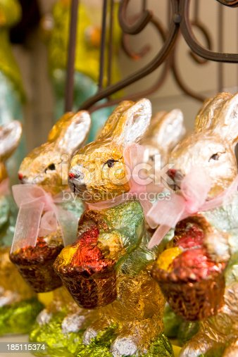 Row of Easter bunnies with baskets wrapped in multi colored aluminum foil waiting for customers. Selective focus.