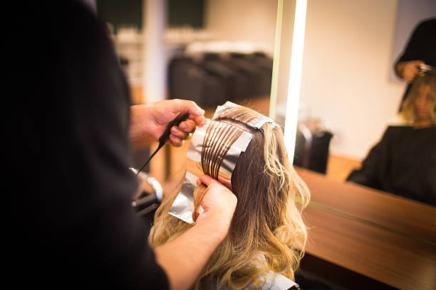 Foiled Highlights Hairdresser prepares foil highlights in woman's hair highlights hair stock pictures, royalty-free photos & images