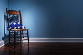 A triangle folder American flag from the coffin of a deceased Veteran with blank dog tags in the spot light, sitting in their old wooden chair with wooden cane that is in the corner of an empty room.