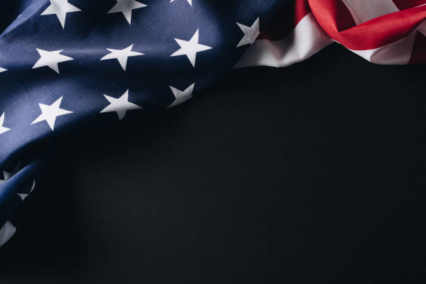 folded american national flag isolated on black, memorial day concept stock photo