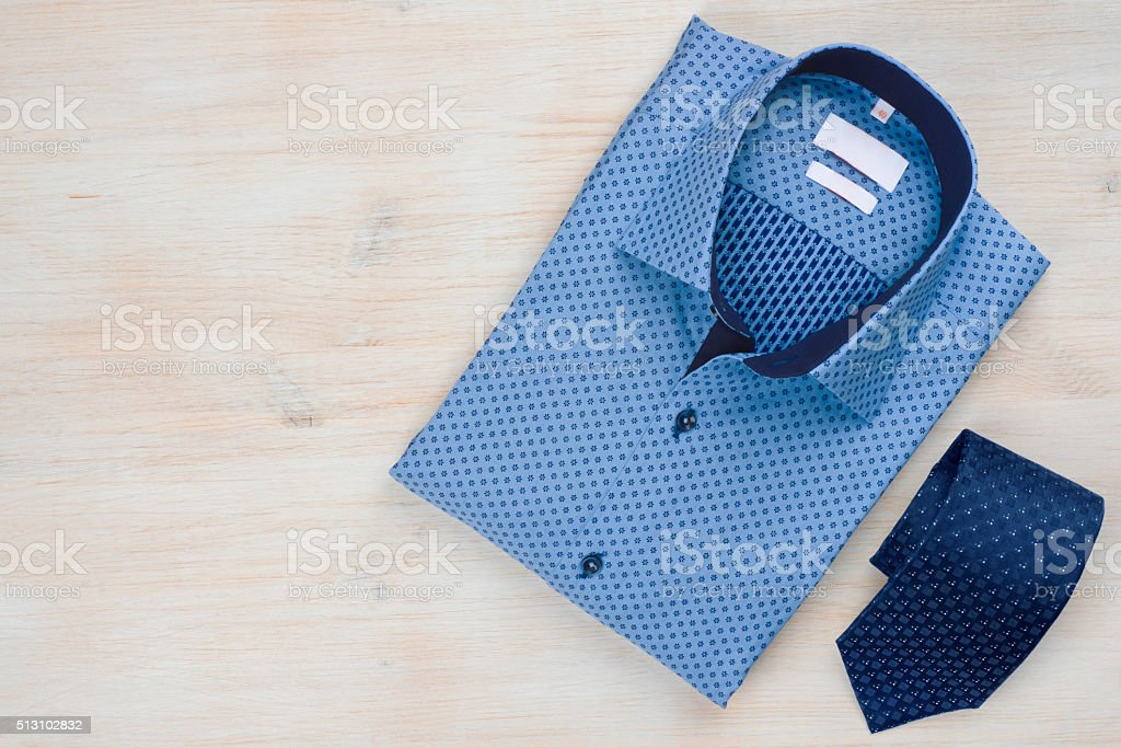Folded blue man shirt and tie isolated on wooden background stock photo