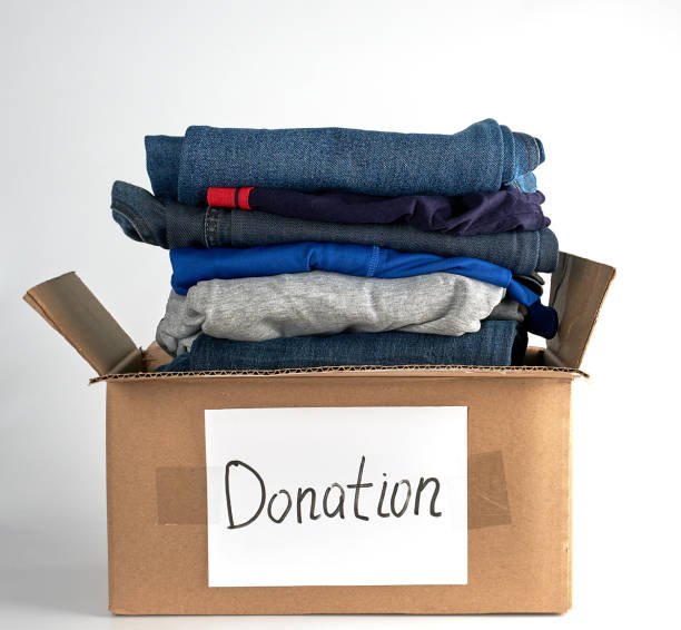 folded clothes in a brown paper box with the inscription donation folded clothes in a brown paper box with the inscription donation  on a white background, the concept of helping people in need clothes in box stock pictures, royalty-free photos & images