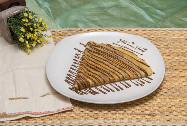 Folded crepe, Russian blini with chocolate sauce on white plate with fabric pouch and yellow flowers stock photo