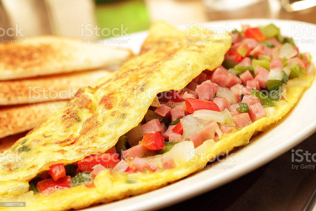 A folded egg omelets filled with chopped ham and vegetables royalty-free stock photo