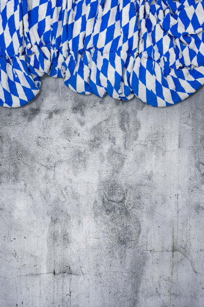 folded flag with bavarian colors of white and blue on empty concrete wall stock photo