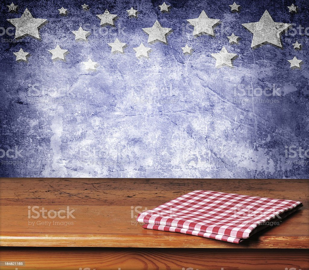 Folded gingham cloth on table with blue starred background  stock photo