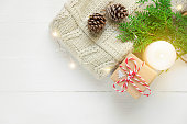 Folded knitted off-white wool sweater gift box pine cones green juniper twig golden lights garland on plank wood table by window. Lit burning candle. New Year Christmas magic atmosphere. Scandi style