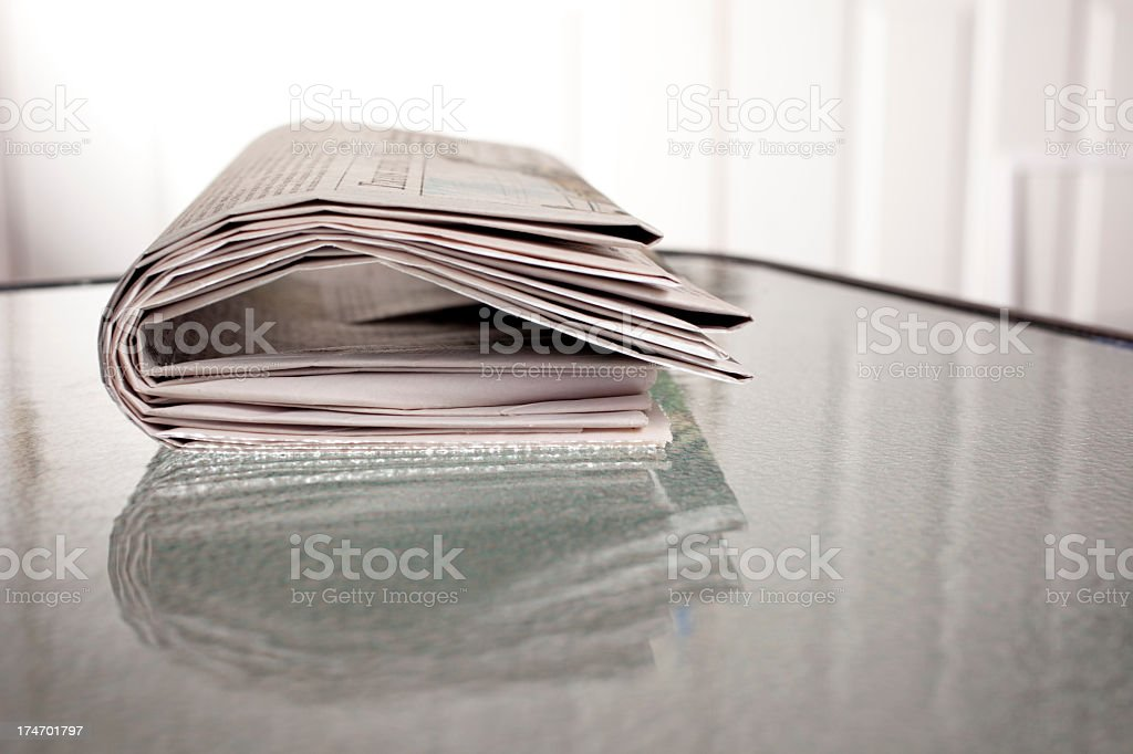 Folded Newspaper  on glass top table with reflection royalty-free stock photo
