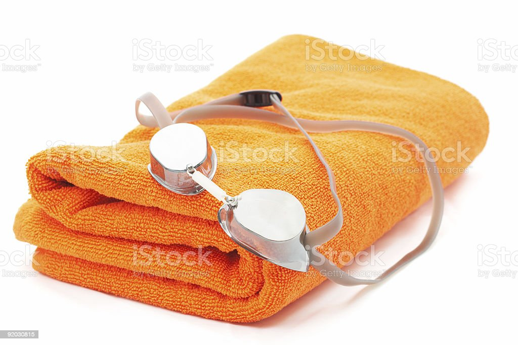 Folded orange towel and pair of goggles stock photo