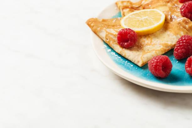 Folded pancakes on white marble background stock photo