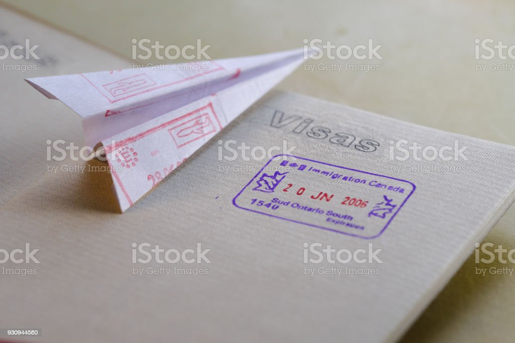 Folded paper airplane with entry stamps and passport stock photo
