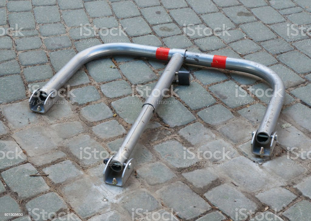 Folded parking barrier on a cobblestone pavement stock photo