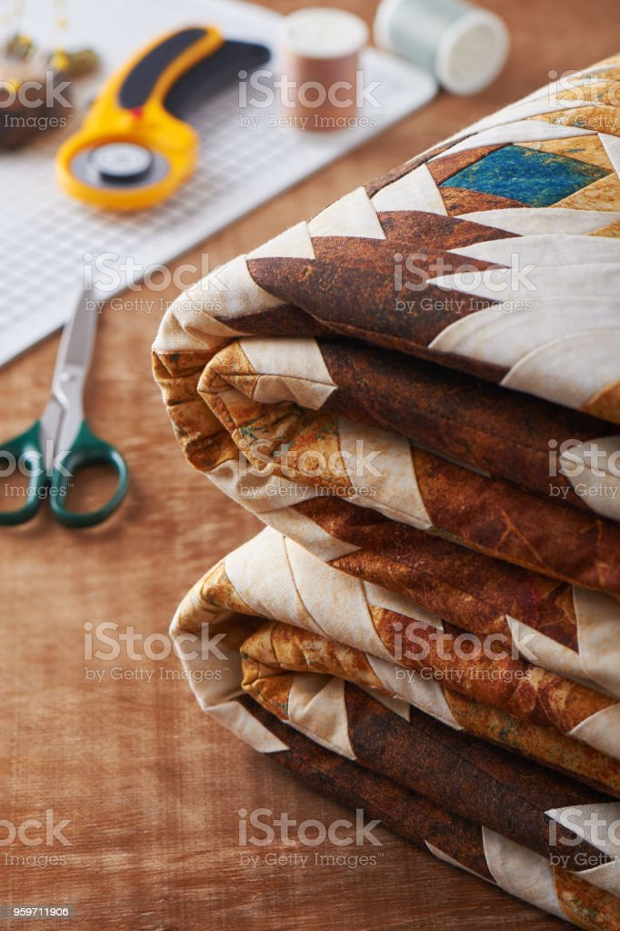 Folded patchwork blanket on wooden surface on sewing accessories background stock photo