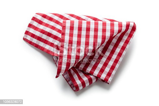 Top view of a folded picnic red cloth isolated on white background. Useful copy space available for text and/or logo. Predominant colors are red and white. High key DSRL studio photo taken with Canon EOS 5D Mk II and Canon EF 100mm f/2.8L Macro IS USM.