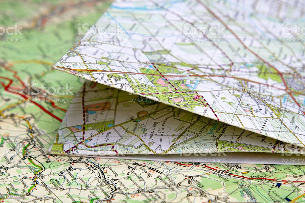 A folded road map laying on a flat road map  stock photo