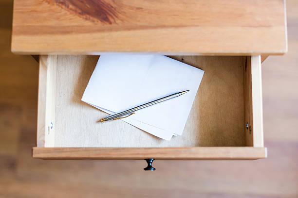 folded sheet of paper and pen in open drawer - schubladenkommode weiß stock-fotos und bilder