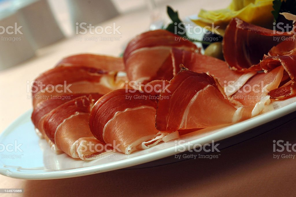 Folded slices of smoked ham served as appetizer close up royalty-free stock photo
