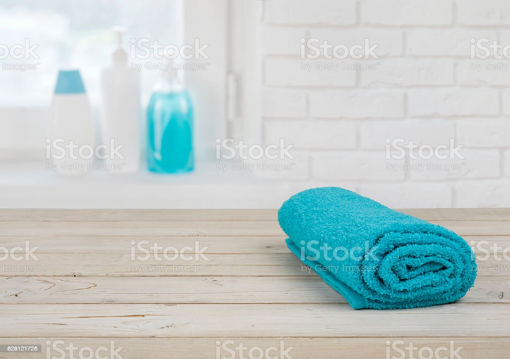 Folded towel on wooden planks over defocused brick wall window stock photo