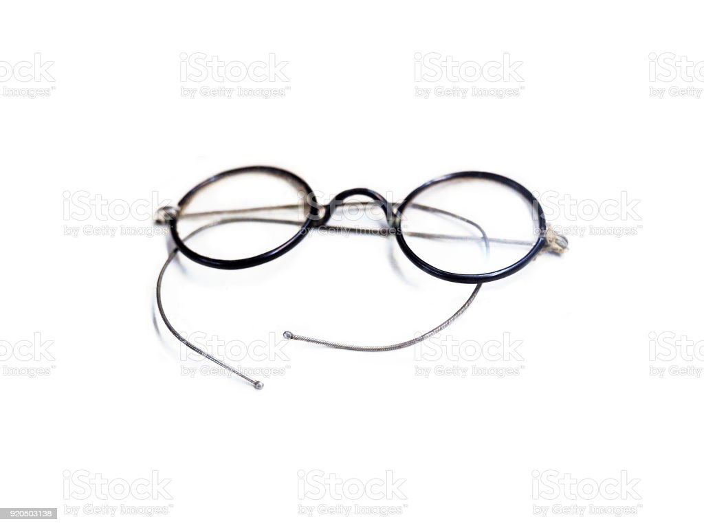 Folded vintage round eyeglasses isolated on white background. Antique black reading glasses with silver spectacles stock photo