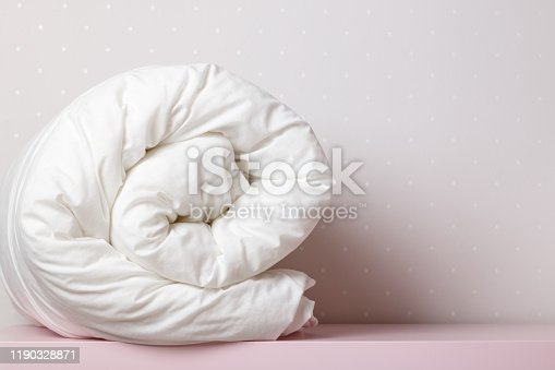 A folded, warm duvet is lying on the dressing table. Quilt for the bed. Copy space.