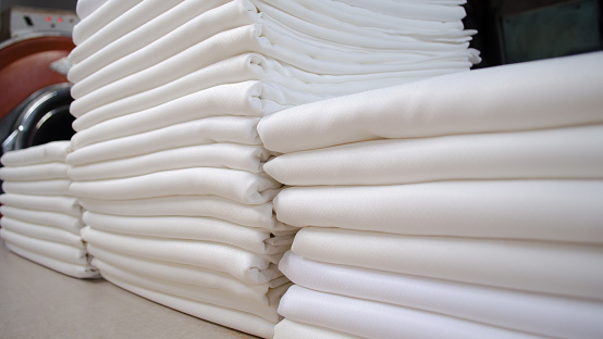 Folded white choths in a laundry.