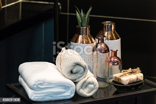 618327092istockphoto folded white towel with cermic vase on glass table 636091908