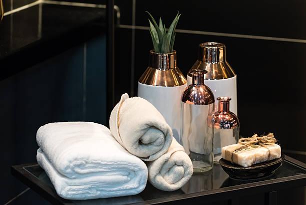 folded white towel with cermic vase on glass table - prodotto per l'igiene personale foto e immagini stock
