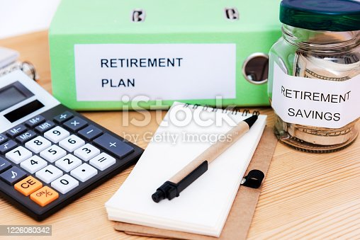 Folder With The Label Retirement Plan, money, calculator, notepad and pan on wooden desk