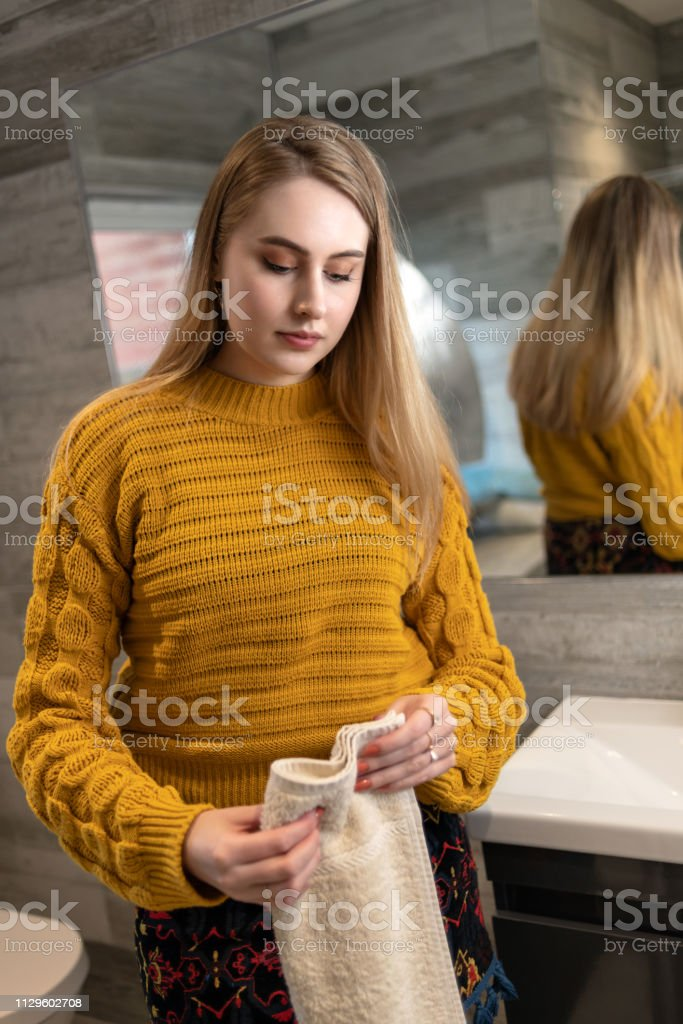 Folding a towel in a bathroom stock photo
