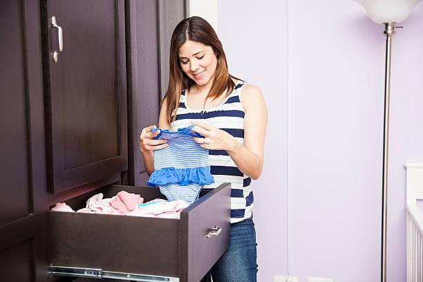 folding baby clothes in a closet - mutterkleiderschrank stock-fotos und bilder