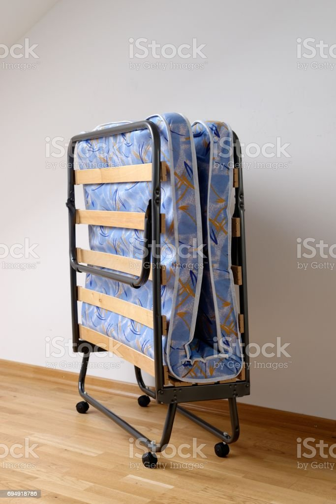 A folding bed in front of a white wall stock photo