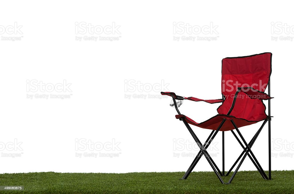 Folding camp chair on grass with white background stock photo