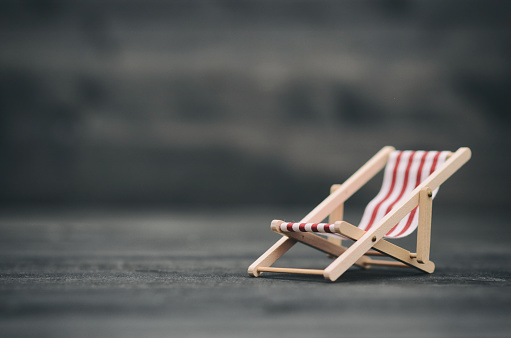 istock Folding Canvas Sun Lounging chair on black wooden background 1215484448