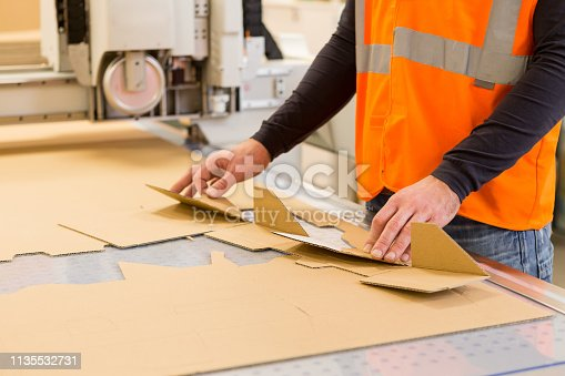 Man Folding cardboard at the printing plant