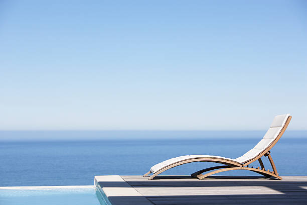 Folding chair on infinity pool deck stock photo