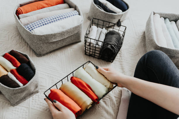 Folding clothes and organizing stuff in boxes and baskets. Concept of tidiness, minimalist lifestyle and japanese t-shirt folding system. Wardrobe storage system. Clean up clothes with konmari method (Marie Kondo). Clothes neatly folded in bedroom arrangement stock pictures, royalty-free photos & images