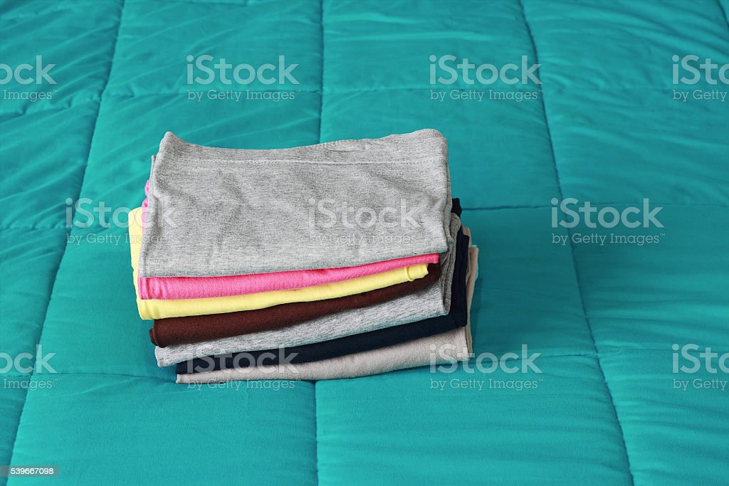 folding clothes on bed before keeping stock photo