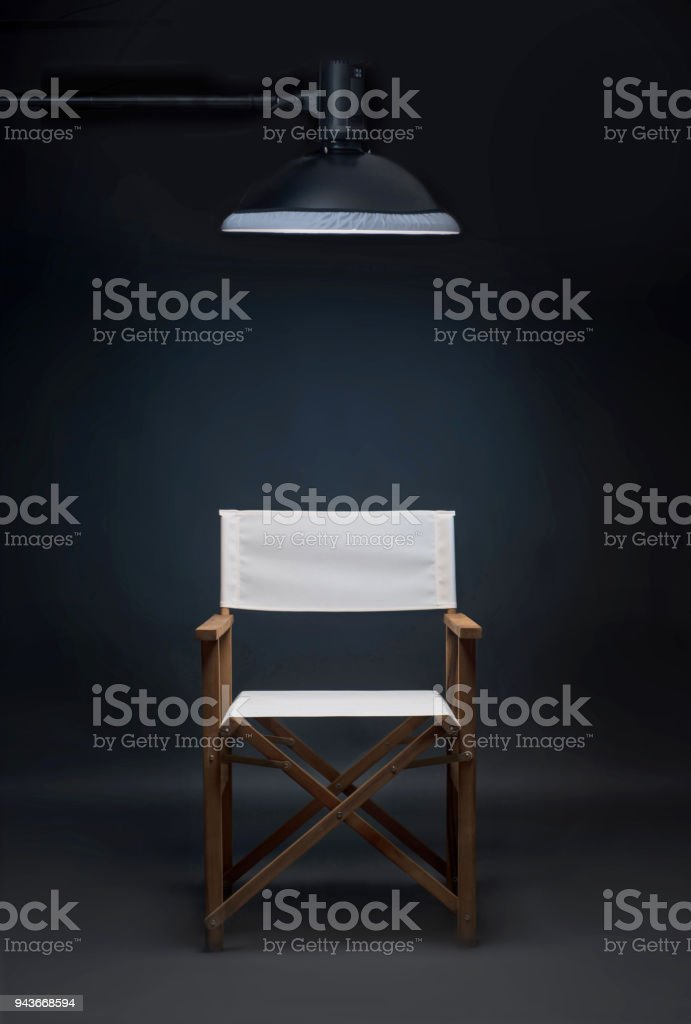 Folding director\'s chair in a photo studio on a blue background.