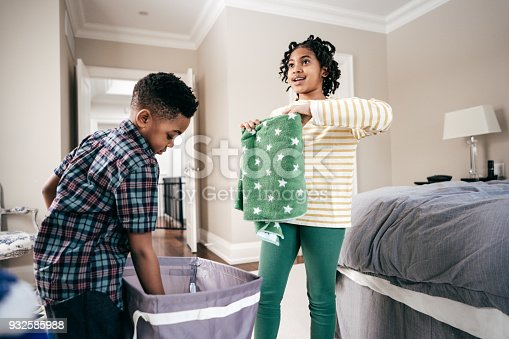 954356678istockphoto Folding towels with sister 932585988