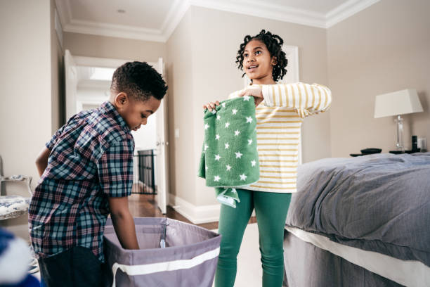 Folding towels with sister Siblings helping with  chores chores stock pictures, royalty-free photos & images