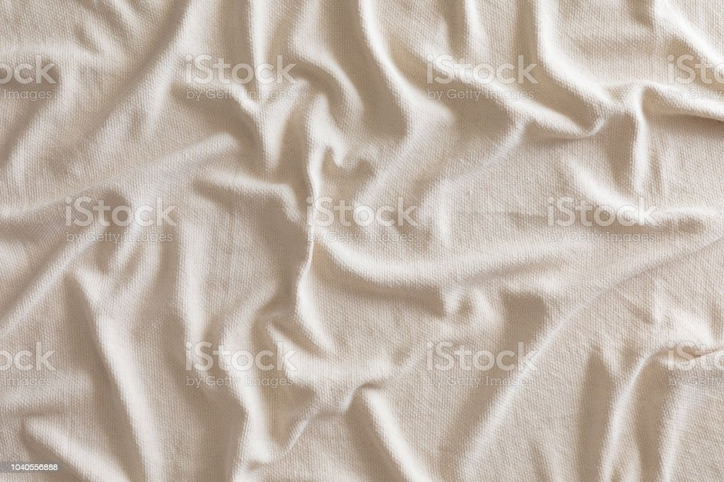 Folds of soft beige plaid or blanket, top view