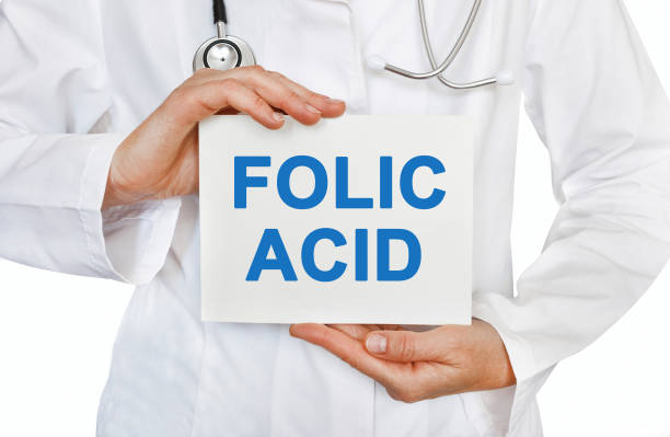 folic acid card in hands of medical doctor - folic acid stock photos and pictures