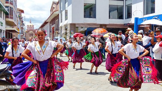 Cuenca, Ecuador - April 11, 2019: Traditional parade or desfile on day of foundation of city Cuenca at the main street Simon Bolivar at historical part of city. Smiling beautiful women folk dancers in typical dress of Azuay province, cuencanas, with colorful scarves of Gualaceo design