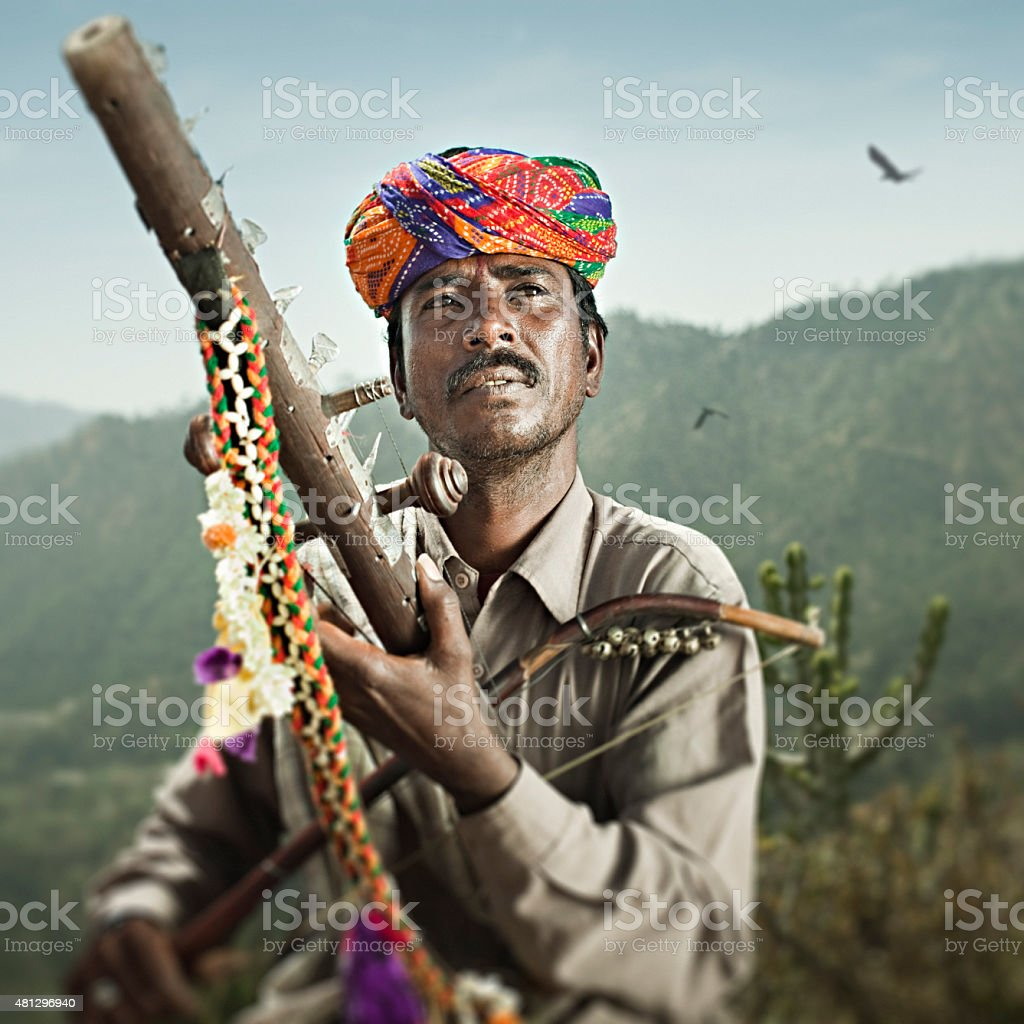 Folk musician of Rajasthan, India playing traditional musical instrument Ravanahatha. stock photo